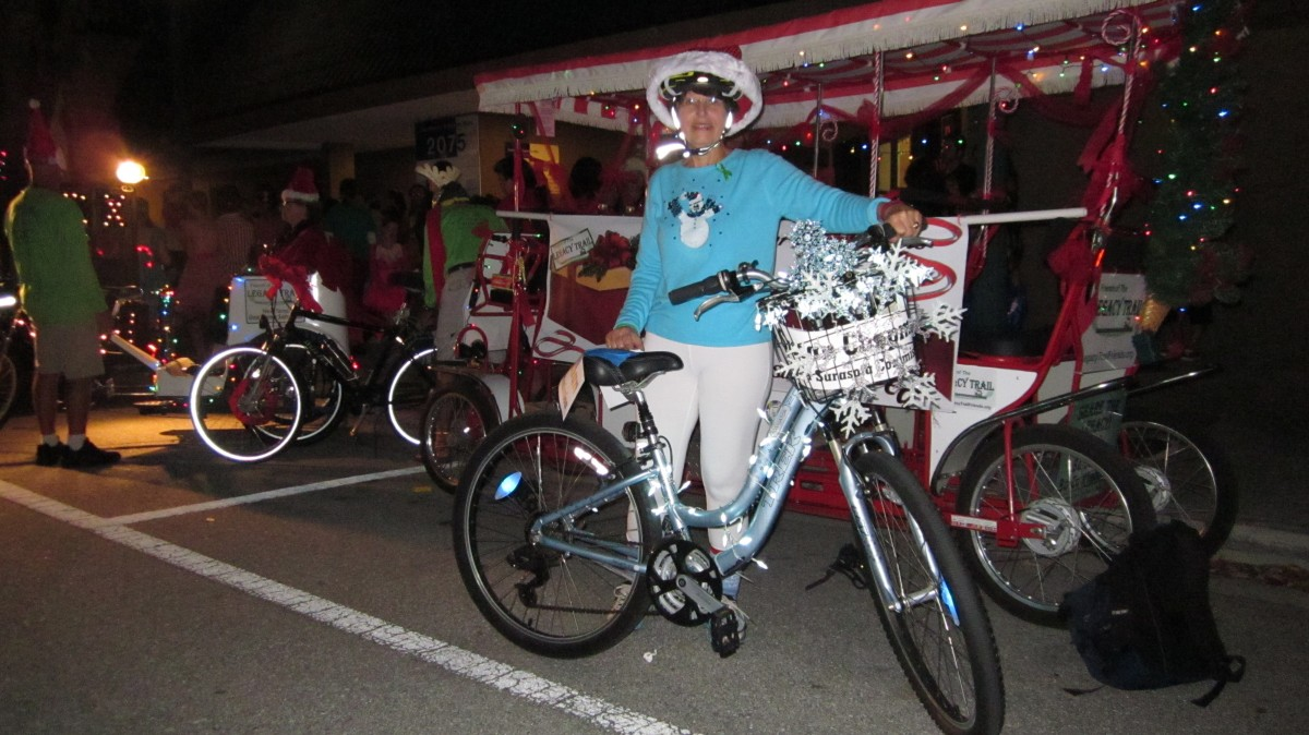 Sarasota city commissioner Susan Chapman rides her brightly decorated bike in the 2015 Sarasota Christmas Parade with FLT.